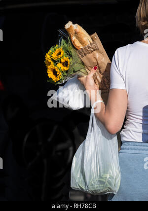 A woman walks having shopped for baguette and sunflowers in Cassis, France - Stock Image