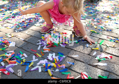 A young girl plays in confetti littering the ground following a festival kick-off ceremony in Rogers, Arkansas. - Stock Image
