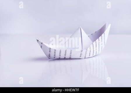 Paper boat sails, on white background - Stock Image