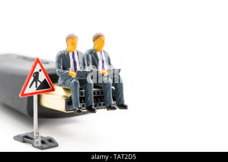 Macro shot on miniature figures as business men working on the laptop notebook sitting on HDMI plug, isolated on white background. Information technol - Stock Image