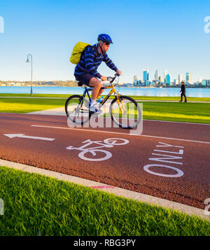 Male cyclist riding down a cycle only bike path / cycle lane with a man walking in the background. - Stock Image