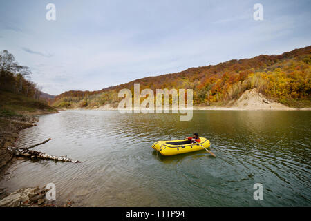 Man rafting in river against sky - Stock Image