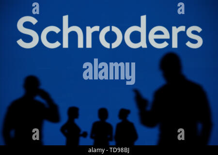 The Schroders logo is seen on an LED screen in the background while a silhouetted person uses a smartphone in the foreground (Editorial use only) - Stock Image