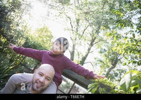 Portrait playful father carrying son on shoulders in backyard - Stock Image