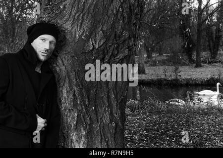 Black and white portrait of handsome man leaning against tree in park with lake and swans in background - Stock Image