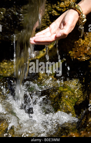 Spring water cascading off rock woman's wet hand, ornamental water feature, Mijas Pueblo, Costa del Sol, Andalucia, - Stock Image