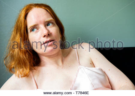 Tilburg, Netherlands. Young, redheaded woman on a Sunday morning, hanging out on her living room sofa waiting up. - Stock Image