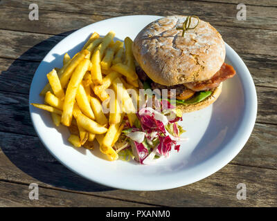 Cafe  lunch  a prime beef burger  with cheese bacon potato chips and salad - Stock Image