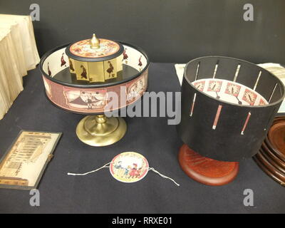 Display of Victorian optical toys including Zoetrope, Praxinoscope with mirrors and Thaumatrope (spinning disc on string) - Stock Image