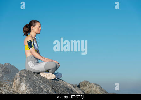 woman wearing sportswear sitting on rocks resting after exercise listening to music on her smartphone - Stock Image