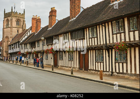 Medieval almshouses line a street in Stratford upon Avon, with a view towards the Guild Chapel. - Stock Image