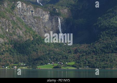 Skjolden, Norway - 6 August 2018: A waterfall on one of the jagged mountain peaks of the Sogenfjorden Fjord on the vicinity of the village of Skjolden in the fjords of Norway on 7 August 2018. The village is set at the inner end of Sogenfjorden, the world's longest fjord and the deepest in Norway with its sheer valley walls and jagged mountain peaks. Photo: David Mbiyu - Stock Image