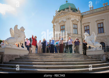 Tour group summer, visitors to the Schloss Belvedere in Vienna listen to their guide during a tour of its famous landscaped gardens, Wien, Austria. - Stock Image