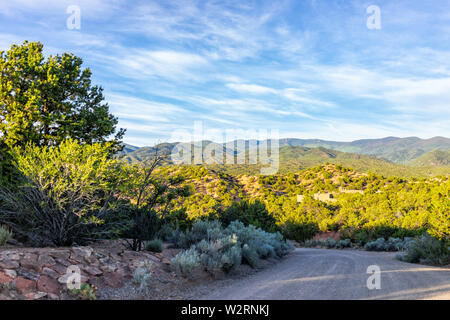 Sunset Santa Fe, New Mexico in Tesuque with golden hour light on green plants and dirt road to residential community - Stock Image