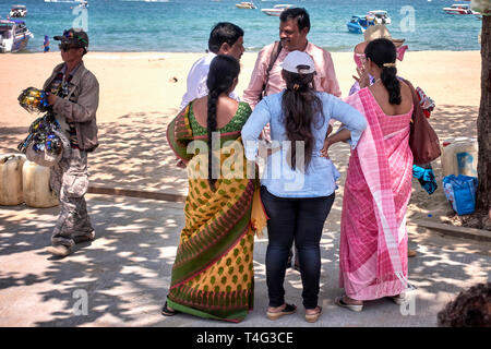 Asian Indian women in traditional Sari dress. Group of Indian tourists. Pattaya beach, Thailand, Southeast Asia - Stock Image