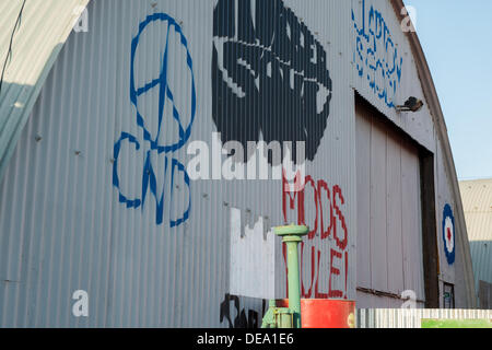 Chichester, West Sussex, UK. 14th Sep, 2013. Goodwood Revival. Goodwood Racing Circuit, West Sussex - Saturday 14th September. Graffiti on an aircraft hanger in the retail area with 'Mods Rule!' and a CND symbol near the retail area. Credit:  MeonStock/Alamy Live News - Stock Image
