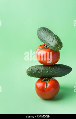Heap of fresh raw organic tomatoes cucumbers stacked one on another in pyramid on chartreuse lettuce green background. Balanced diet vegan healthy lif - Stock Image