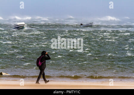 A walker battles against the wind on a Northumberland beach during Storm Ali. Low Newton by the Sea, Northumberland, UK. 19th September 2018. - Stock Image