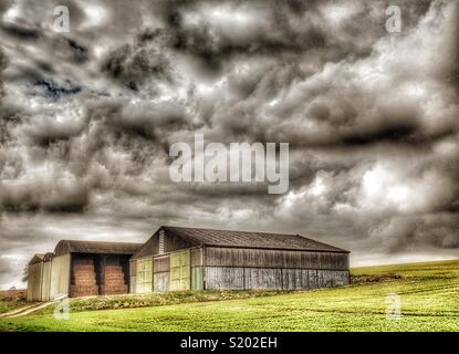 Barns in field with an angry sky, Yorkshire Dales,England, UK - Stock Image