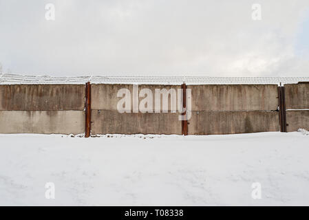 An area surrounded by dirty wired wall in winter. - Stock Image