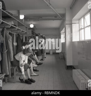 1950s, historical, young ladies at a teacher training college in a changing rom putting on sports shoes for a netball class England, UK. - Stock Image