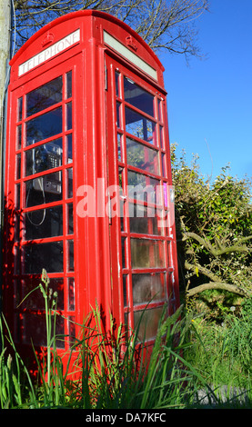 Traditional Red British Telephone Box or booth in a country setting - Stock Image
