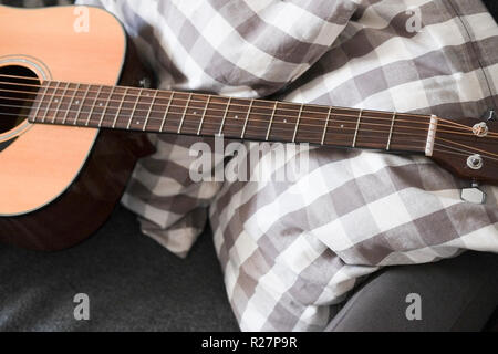 Acoustic guitar lying on a sofa - Stock Image