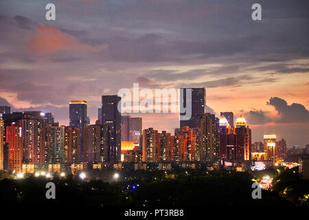High-rise buildings in Futian District illuminated at dusk. Shenzhen, Guangdong Province, China. - Stock Image