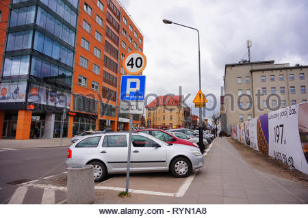 Poznan, Poland - March 8, 2019: Row of parked cars on paid parking spots close by office building on the Slowackiego street in the city center on a cl - Stock Image