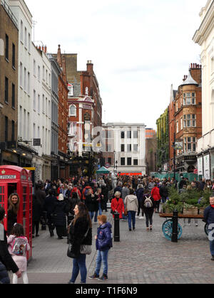 Looking towards the tube station at the crowds of people on a busy Saturday Morning in Covent Garden, London UK - Stock Image