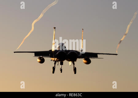 493rd Fighter Squadron F-15C landing at Lakenheath at dusk in sub-zero temperatures causing long wing tip vortices. - Stock Image