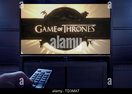 A man points a TV remote at the television which displays the Game of Thrones main title screen (Editorial use only). - Stock Image