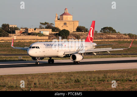 Turkish Airlines Airbus A321 commercial jet airplane on the runway upon landing in Malta at sunset. Air travel and tourism in Mediterranean Europe. - Stock Image