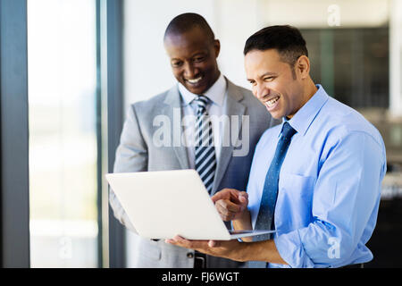 two businessman using laptop in modern office - Stock Image