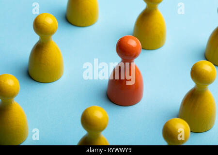 Red And Yellow Pawns Arranging In A Row Over Blue Background - Stock Image
