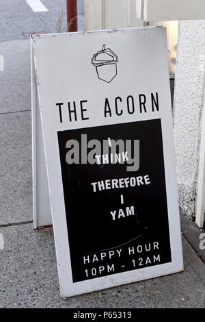 Humorous sandwich board sign on the sidewalk outside a vegetarian and vegan restaurant on Main Street in Vancouver, BC, Canada - Stock Image