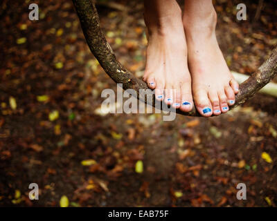 Girl stands on vine swing hanging from trees in forest - Stock Image
