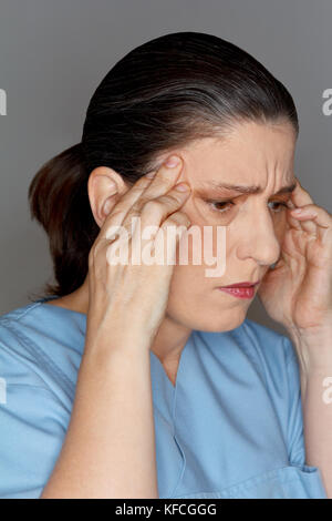 Female nurse or doctor suffering from an acute headache or migraine attack due too much stress and work - Stock Image