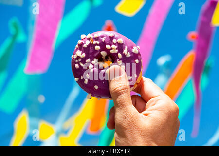 an appetizing donut, coated with a purple frosting and white sprinkles, in the hand of a young man against the sky, where many flags of different colo - Stock Image