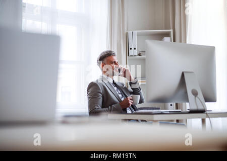 Businessman with smartphone, coffee and computer sitting at the table, making a phone call. - Stock Image
