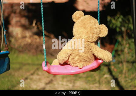 Back view of a teddy bear on a swing in a garden on a sunny day - Stock Image
