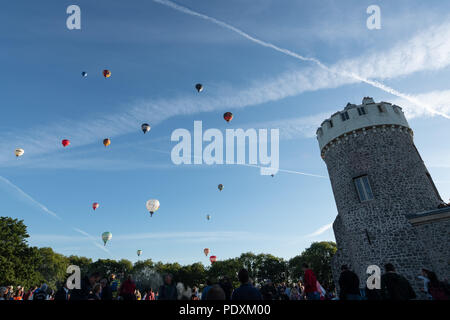 Bristol, UK, 11th August, 2018. Crowds photographing Hot Air Balloons flying over the Clifton Observatory, after the first Mass Ascent from the Bristol Balloon Fiesta 2018. Credit: Steve Davey/Alamy Live News. - Stock Image