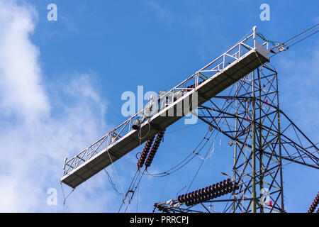 Large temporary work platform attached to an electricity pylon to allow work to be done on pylon and power lines - Stock Image