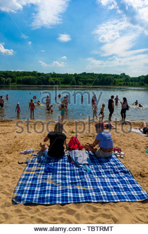 People sitting on a blanket at a crowded lake - Stock Image