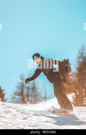 Skier in high mountains, group of funny friends slide downhill together on mountain holiday - Stock Image