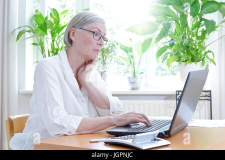Senior woman in her living room staring annoyed at the screen of her laptop,computer or financial problems - Stock Image