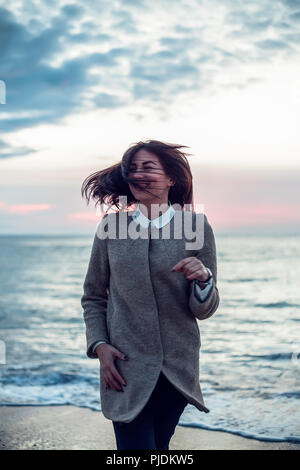 Portrait of young woman standing on beach, her back to the ocean, wind blowing her hair, smiling - Stock Image