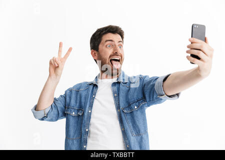 Portrait of a handsome bearded man wearing casual clothes standing isolated over white background, taking a selfie - Stock Image
