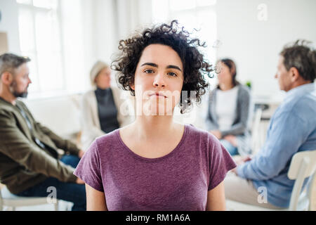 A portrait of young depressed woman during group therapy. - Stock Image