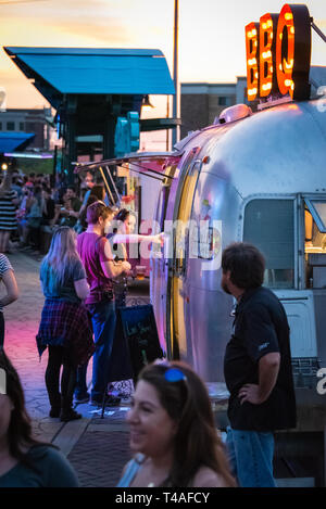 Creative South attendees ordering Southern cuisine from a BBQ food truck on the Pedestrian Bridge over the Chattahoochee River in Columbus, GA. - Stock Image